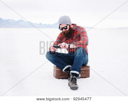 bearded hipster with smart phone and suit case in the salt flats looking for directions