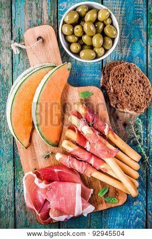 Breadsticks With Prosciutto, Melon, Olives And Bread