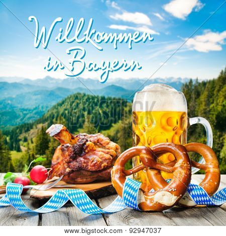Roasted pork knuckle with pretzels and beer. Background with German text Welcome in Bavaria