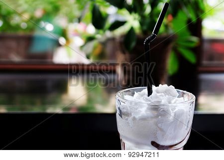 Tasty creamy cocktail in glass, on table, on bright background