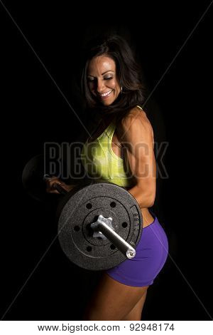 Woman Blue Shorts And Green Sports Bra On Black Barbell Curl Side Smile