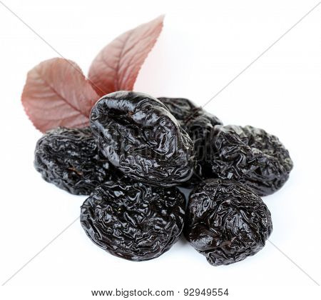 Pile of prunes with leaves isolated on white