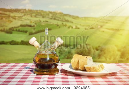 Olive oil and bread on the wooden table against Tuscan landscape. Italy