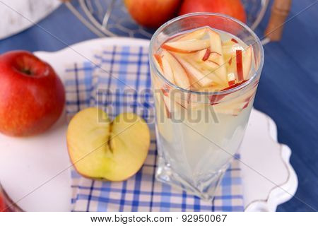 Glass of apple cider with fruits on table close up
