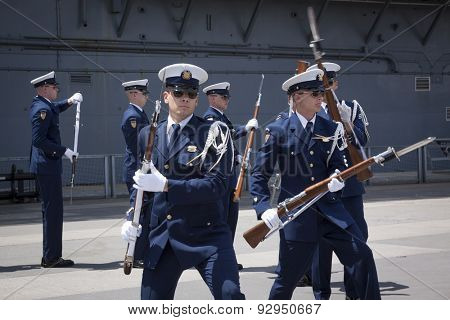 NEW YORK - MAY 22 2015: The US Coast Guard Ceremonial Honor Guard Silent Drill Team lunge forward during a drill on Pier 92 next to the Intrepid Sea, Air, and Space Museum during Fleet Week NY 2015.
