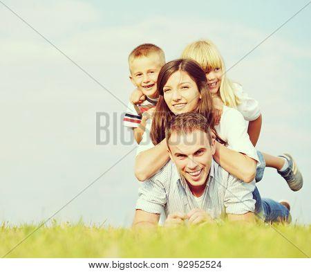 Cheerful family on beautiful summer meadow enjoying and having fun