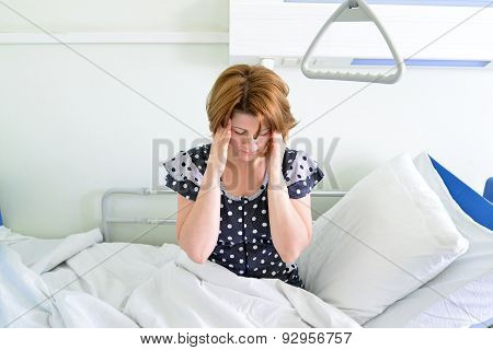 Female Patient With Headache On Bed In Hospital Ward