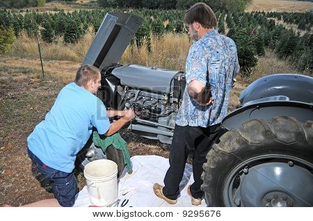 Two Men Fixing Tractor