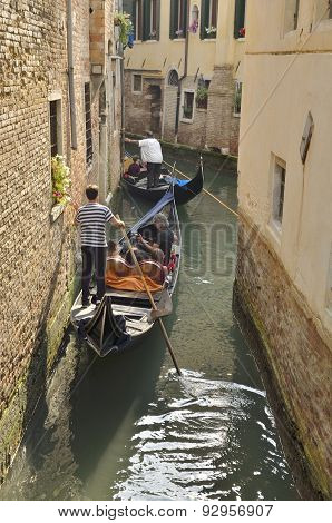 Gondolas Passing By A Narrow Canal