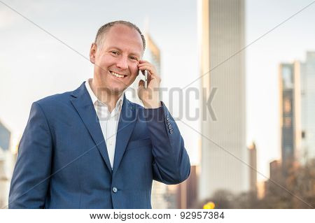 Businessman using phone outside the offices