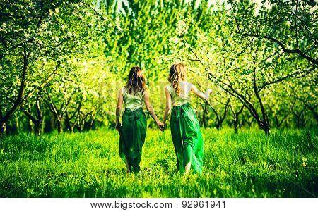 Two Happy Pretty Girls Walking On The Apple Trees Garden