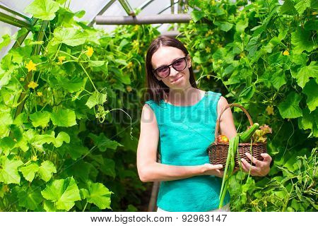 Young woman holding a basket of greenery and vegetables in the greenhouse