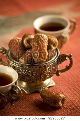 Arabic dates in an ornamental bowl and tea cups. Arabain refreshment.