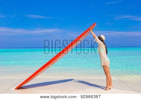 Happy beautiful surfer girl at white beach with her surfboard
