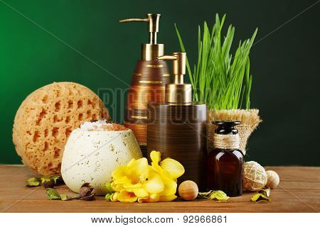 Composition of spa treatment on wooden table, on dark green background