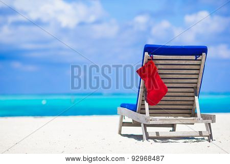 Sun chair longue with red Christmas stocking on tropical white beach and turquoise water