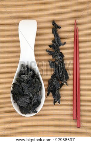 Wakame edible seaweed with chopsticks over bamboo background.
