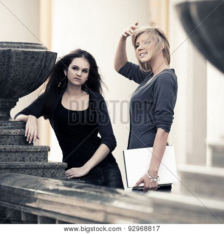Two happy young fashion female students at university building