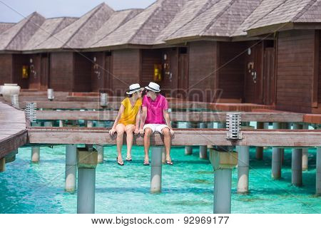 Young couple on beach jetty near water villa in honeymoon