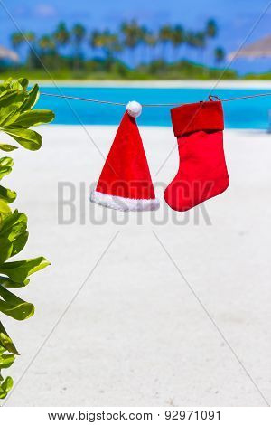 Red Santa hat and Christmas stocking hanging on tropical beach. Christmas concept.