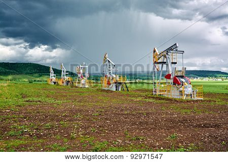 Pumping Unit For Pumping Oil On A Background Of Cumulus Clouds And Rainfall