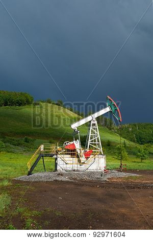 Pumping Unit For Pumping Oil On A Dark Blue Storm Clouds