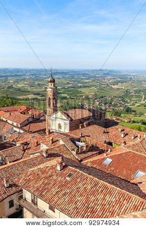 Church and red roofs in town of La Morra as green hills on background in Piedmont, Northern Italy.