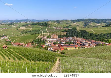 Small town of Barolo among green hills and vineyards under blue sky in Piedmont, Northern Italy.