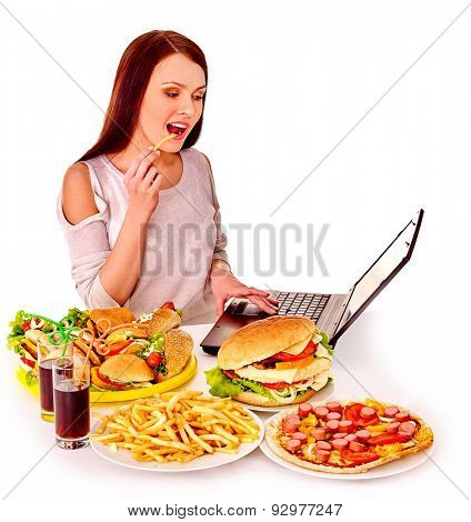 Woman eating fast food at work on laptop. Isolated.