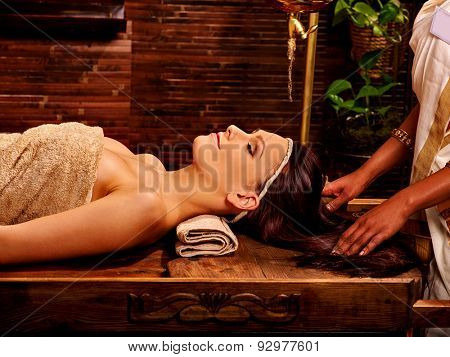 Woman having facial  spa treatment on wooden massage table.