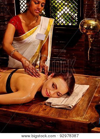 Young woman having oil spa Indian treatment.