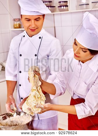 Happy woman and man in chef hat cooking dough  on professional kitchen.