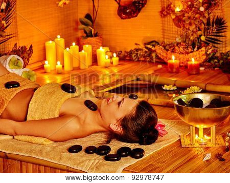 Woman getting stone therapy massage in bamboo spa. Stone therapy with burning candle.
