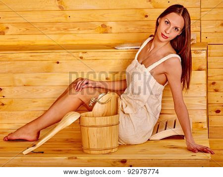 Young woman in sauna. Girl looking in camera.