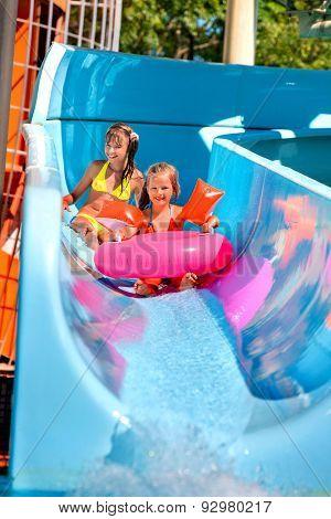 Kids on blue water slide at aquapark. Summer holiday.