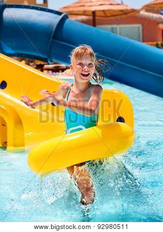 Children sitting on yellow inflatable ring in swimming pool.