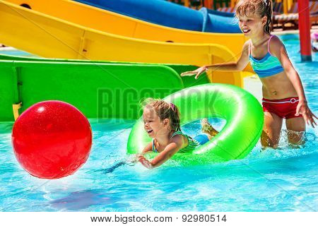Child on water slide at aquapark.Playing with beach ball on summer holiday.