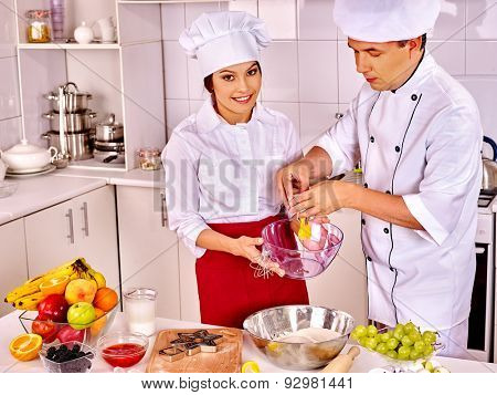 Happy woman and man in chef hat cooking dough .