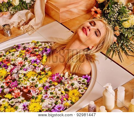 Woman with close eyes relaxing at water spa.