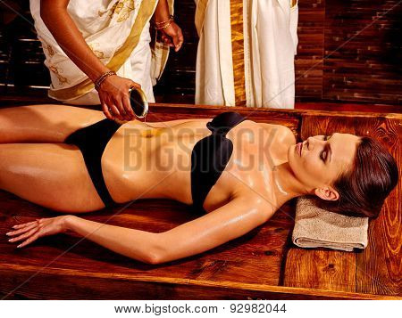 Young woman having stomach pouring oil Ayurveda spa treatment.