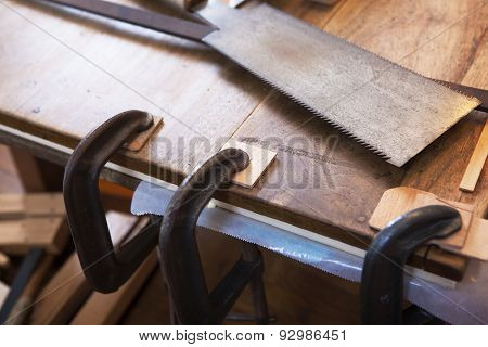 Wood working. Saw, clamps in use and wood on a work bench