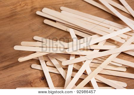 Educative craft. Popsicle sticks on wooden desk. Shallow depth of field.