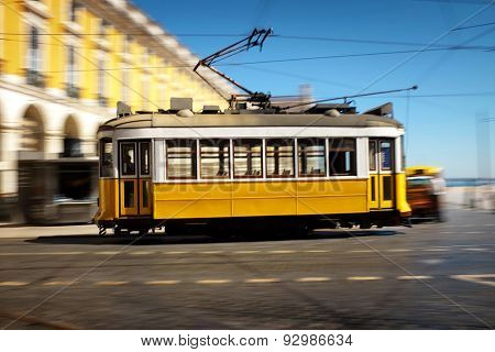 Lisbon traditional old electric tram speeding in Comecio Square