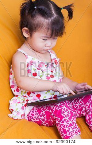 Little Asian Girl Using Digital Tablet, Child Finger Point At Computer Tablet, Studio Shot