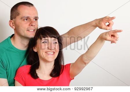 Smiling Couple Looking And Pointing Into Distance