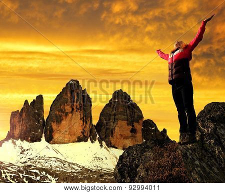 Girl on a rock, in the background Tre Cime di Lavaredo at sunset ,Dolomite Alps, Italy