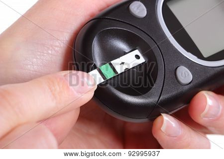 Closeup Of Glucose Meter And Finger