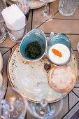 stock photo of pesto sauce  - Ceramic saucers with Italian pesto sauce white cream souce and bread on a plate - JPG