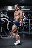 pic of hamstring  - Strong Athletic Man Fitness Model Torso showing muscles in gym - JPG