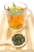 foto of nettle  - Fresh nettle with white flowers cup of hot beverage and dried nettle on wooden spoon nettle brewed in cup - JPG